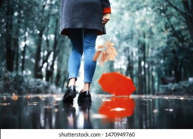 autumn landscape in the park girl with a red umbrella / concept autumn weather raining, a young woman under an umbrella