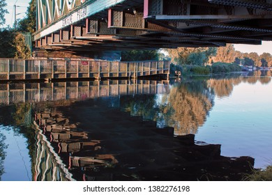Autumn landscape of reflections in water of the River Cam under the railway bridge in East Chesterton, Cambridge. With wooden walkway into countryside beyond.