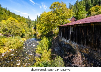 Autumn landscape of a river flowing through a small town with an old building on the side.