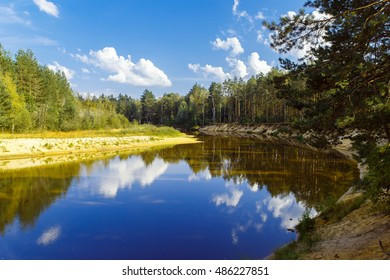 Autumn landscape. The river flows through the forest, blue sky with clouds.