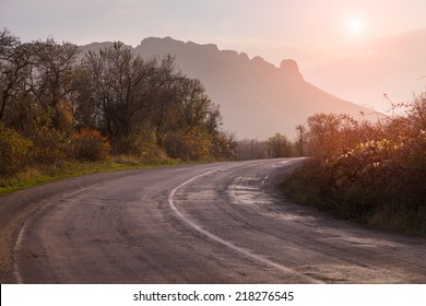 Autumn landscape with road. The gold light beams sunrise. On a background of mountains and the sky with clouds.
