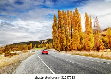 Autumn landscape with road and red car, New Zealand