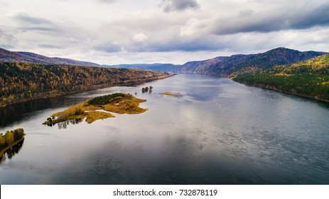 Autumn landscape in Siberia, flight over islands on the Yenisei River, shooting from air. soft focus