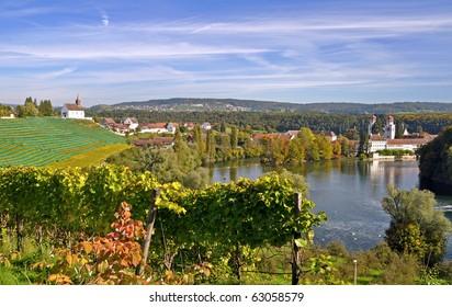 Autumn landscape in Switzerland - River Rhine with old abbey of Rheinau