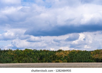 An autumn landscape. A view of the green country agricultural field against stormy blue sky.