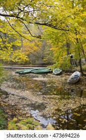 Autumn landscape: yellow leaves fall on the water and green boats