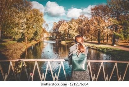autumn landscape, yellow trees, a girl stands on a bridge in the park