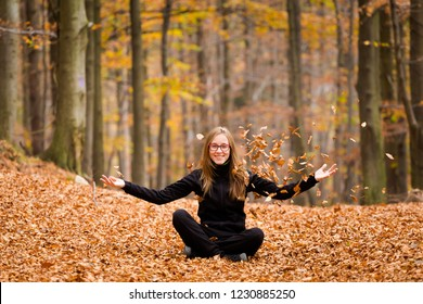 Autumn landscape with young caucasian girl playing with leaves taken in polish Beskidy mountains during colorful autumn, Grabowa.