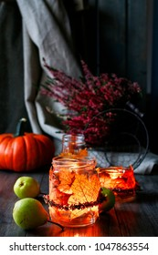 Autumn lantern made of glass jar decorated with colorful leaves and heather wreath. Candle inside.