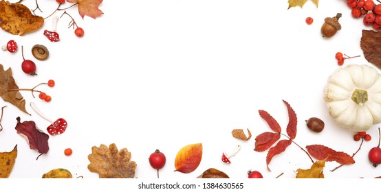Autumn layout composition frame of dry leaves of twigs, pumpkin and berries on white background, Flat lay, top view, copy space, halloween concept.