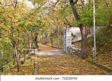 Autumn, leaf fall. Scenic view to a old paved road through the forest on the slope of Mashuk Mountain in Pyatigorsk, Russia. On the right is the building of the old pumping station of mineral water
