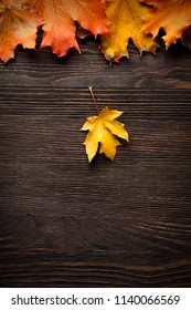 autumn leaf on wood black background (top view) orange leaf on old grunge wood deck, copy place for inscription, tablet for text,