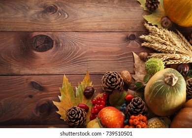 Autumn leafs with berries and vegetables on grey wooden table