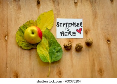 Autumn leaves with an apple and September is here text on a note on wooden table
