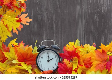 Autumn Leaves Background, Autumn Leaves and Alarm Clock with grunge wood with space for your message