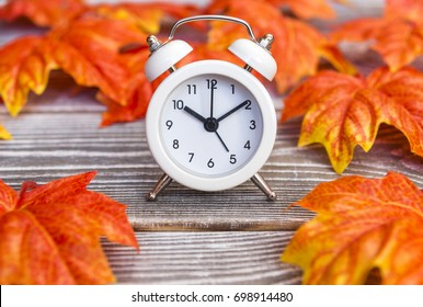 Autumn Leaves Background, Autumn Leaves and Alarm Clock with grunge wood with space for your message. The idea of autumn has come
