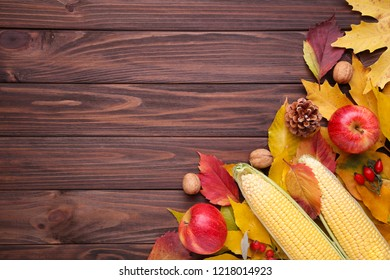 Autumn leaves with berries and vegetables on a brown wooden table. Thanksgiving day