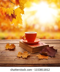 Autumn leaves, book and cup of tea on wooden table. Autumn mood background.