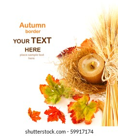 Autumn leaves border with candle & wheat isolated on white