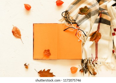 Autumn leaves composition concept background. Open book for text layout, mock up , scarf in a cage, glasses and autumn leaves on a light vintage background. Flat lay. Top view. Copy space