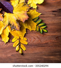 Autumn leaves corner frame on wooden background