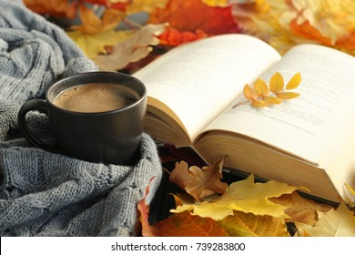 Autumn leaves, cup of coffee, warm scarf and opened book on the table. Seasonal, book reading, Sunday relaxing and still life concept. Selective focus.