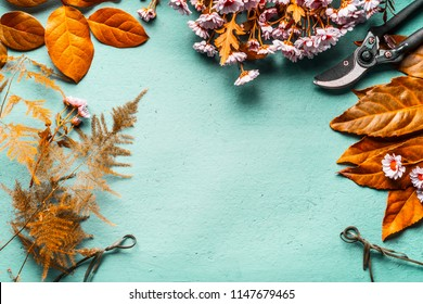 Autumn leaves decoration and flowers arrangement background with yellow leaves and pink flowers on turquoise desktop , top view. Autumn florist work space flat lay. Fall layout frame with  copy space