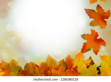 Autumn leaves form a bborder against a bokeh background with sunflare and seasonal colors. Copy space. Good for Halloween and Thanksgiving.