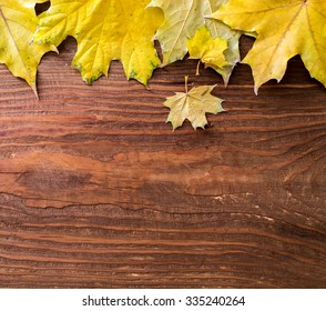 Autumn leaves on brown wooden background as top frame