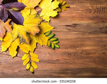 Autumn leaves on old wooden grunge background