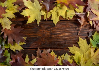 Autumn leaves on wooden table background Frame of autumn