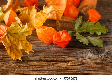 Autumn leaves on wooden table. Autumn vintage background. Red and yellow dried autumn leaves, cute details of cold season.