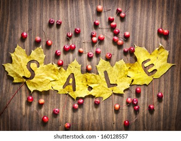 """Autumn leaves over wooden background with word """"Sale"""" and   little red apples"""