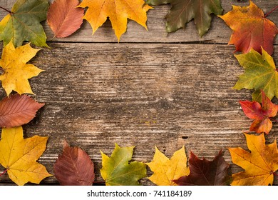 Autumn leaves over wooden background with copy space. top view, frame, banner