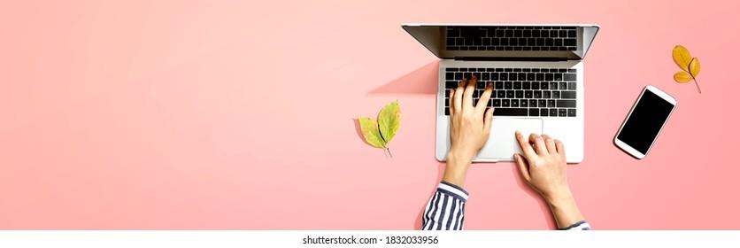 El otoño sale con una persona que usa un ordenador portátil desde arriba