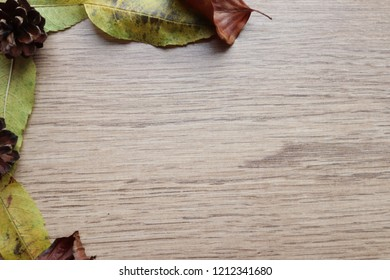 Autumn leaves and pine cones around the edge of wood. Copy space, background ,frames and wallpaper images