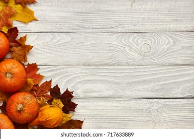 Autumn leaves and pumpkins over old wooden background with copy space