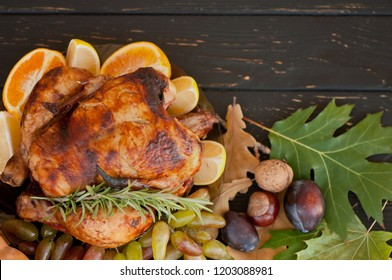Autumn leaves, roast chicken, nuts, chestnuts, plums and grapes on a dark wooden background. Thanksgiving Day. Banner. Top view. Flat lay