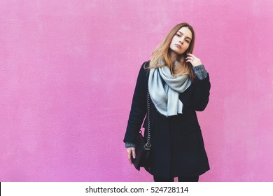 Autumn lifestyle fashion portrait of young woman posing near street wall, wearing cute trendy jacket, skirt and black big handbag