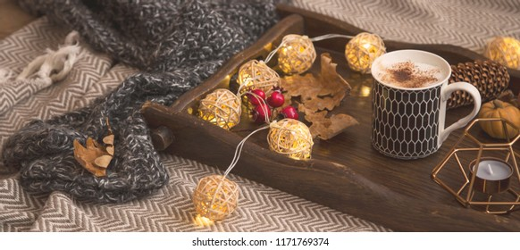 Autumn lifestyle home decor with woolen sweaters and blanket, wooden tray with hot chocolate cup and autumn decorations, warmy lights home interior decor