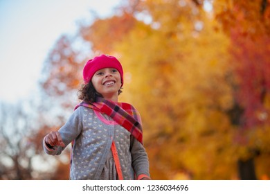 Autumn Lifestyle image of a girl in park wearing a red had and scarf
