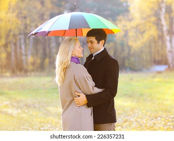 Autumn, love, relationships and people concept - lovely pretty couple with colorful umbrella in the park