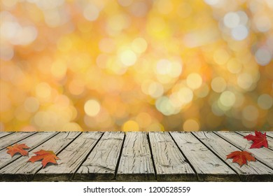 Autumn Maple leaves on rustic wooden deck with nice bokeh in autumn tone in background. For display or montage your products.