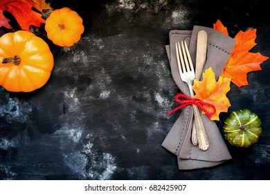 Autumn menu concept - rustic table place setting with a fork and a knife wrapped in a napkin with fall season decorative leaves and pumpkins with copyspace