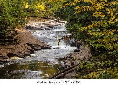 Autumn Michigan Waterfall. Waterfall in the Porcupine Mountains of Michigan's Upper Peninsula framed by autumn foliage.