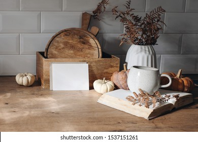 Autumn mockup scene. Blank card, open book, cup of coffee, wooden chop boards and dry fern leaves in sunlight. Fall kitchen still life with pumpkins. Wooden table background. Thanksgiving, Halloween.