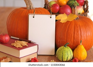 Autumn mockup.empty  notebook with   maple leaf,two large orange pumpkins,books , basket with apples and pumpkins on a wooden table . copy space. Autumn season.Autumn mood.