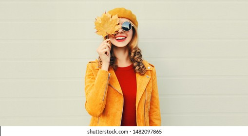 Autumn mood! happy smiling woman holding in her hands yellow maple leaves hiding her eye over gray wall background