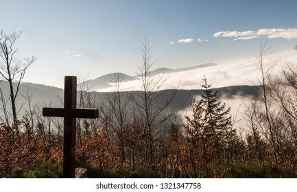autumn Moravskoslezske Beskydy mountains scenery from hiking trail bellow Lysa hora hill in Moravskoslezske Beskydy mountains in Czech republic with cross, hills, mist and blue sky above