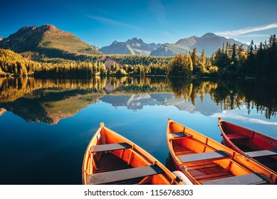 Autumn morning by lake in mountains. Boats, nature, water. Strbske pleso, High Tatras, Slovakia